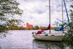立陶宛,特拉凯2017年 10 在Galve湖的19白色小船和特拉凯在背景防御 特拉凯城堡是哥特式样式和现在 免版税库存图片