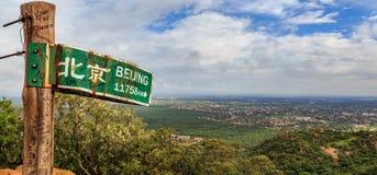 竖立路标到小山的北京在哈博罗内市,博茨瓦纳附近 免版税图库摄影