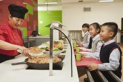 站在队中在学校食堂的小学生 免版税库存照片