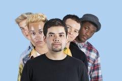 站在队中在蓝色背景的不同种族的朋友画象  库存照片