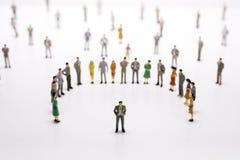 站在队中小组在白色背景的微型的人 免版税图库摄影