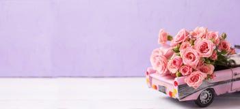 站点的长的横幅 有桃红色玫瑰的减速火箭的汽车玩具开花agai 库存照片