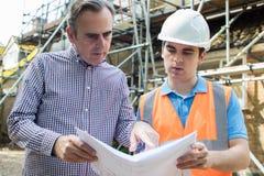 站点的顾客谈论计划与建造者 免版税库存照片