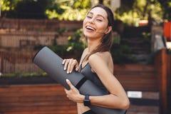 站立一个微笑的年轻健身的女孩的画象户外 免版税库存图片