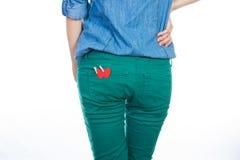 站立一件蓝色牛仔布的衬衣和绿色的牛仔裤的一名妇女隔绝在与红色纸心脏的白色背景在您的后面口袋 免版税库存图片