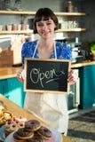 站立与一个开放标志的微笑的女服务员 库存图片