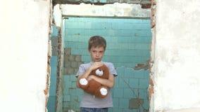 站立与一个软的玩具的肮脏的矮小的孤儿男孩 股票录像
