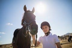 站立与一匹马的车手女孩在大农场 库存图片