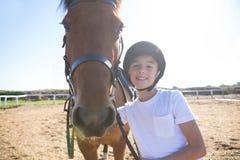 站立与一匹马的车手女孩在大农场 免版税库存照片