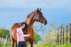 站立与一匹马的年轻美丽的女孩在苹果树 库存图片