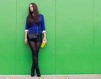 站立与一块玻璃的美丽的深色的女孩在他的手上在绿色墙壁附近 免版税图库摄影