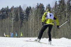 站立与一条腿的一个女性滑雪者的全长画象在滑雪倾斜上升了在一个晴天反对滑雪电缆车 冬天vacat 免版税库存图片