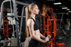 站立与一条跨越横线的黑上面的少妇在他的手上在健身房 免版税库存图片