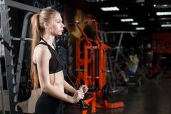 站立与一条跨越横线的黑上面的少妇在他的手上在健身房 库存照片
