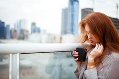 站立与一杯咖啡的夹克的红发女孩在摩天大楼背景的  平衡 库存照片