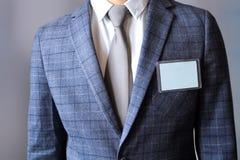 站立与一枚空白的徽章的商人 库存图片