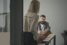 站立与与坐在桌上的人同事的黏合剂的妇女 商人在会议期间在会议室 免版税库存照片