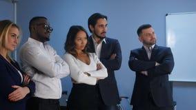 站立与严肃的神色的企业队在办公室 免版税库存照片