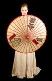 站立与中国伞的维多利亚女王时代的礼服的女孩 免版税库存照片