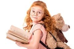 站立与书和玩具熊的红色头发孩子 免版税库存照片