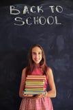 站立与书的高进取者女小学生反对黑板 免版税库存照片