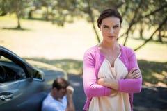 站立与人的恼怒的妇女坐乘故障汽车 库存图片