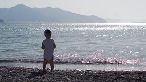 站立与他的一个逗人喜爱的小孩回到照相机投掷小卵石入海 影视素材