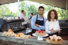 站立与剪贴板的侍者和女服务员在柜台在餐馆 库存图片