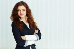 站立与双臂的美丽的年轻女实业家被交叉 免版税库存照片