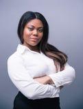 站立与双臂的非洲女实业家被交叉 免版税库存照片