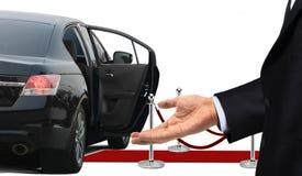站立与受欢迎的姿态的司机在大型高级轿车旁边 图库摄影