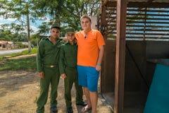 站立与古巴士兵的十几岁的男孩 库存照片
