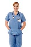 站立与听诊器的微笑的女性护士 免版税库存照片