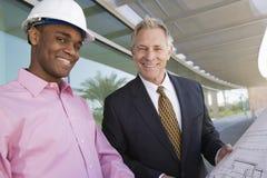站立与图纸的商人和建筑师 免版税库存图片