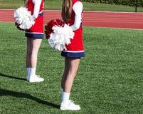 站立与在他们后的大型机关炮的两位高中啦啦队员 免版税图库摄影