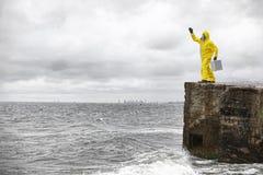 站立与在具体风雨棚的银色案件的防护套服的专家 免版税库存照片
