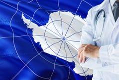 站立与在南极洲旗子背景的听诊器的医生 全国卫生保健系统概念,医疗题材 库存照片