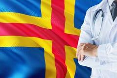 站立与在奥兰群岛旗子背景的听诊器的医生 全国卫生保健系统概念,医疗题材 免版税库存照片