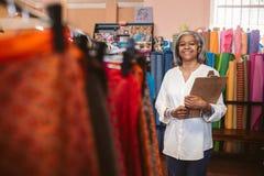 站立与在她的织品的一张剪贴板的微笑的妇女购物 免版税库存照片