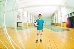 站立与在学校健身房的足球的男孩 免版税库存照片