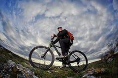 站立与在岩石的自行车的年轻骑自行车者的画象反对与云彩的剧烈的天空 库存照片