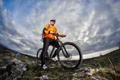 站立与在岩石的自行车的年轻骑自行车者的画象反对与云彩的剧烈的天空 库存图片