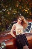站立与在时尚礼服的一辆减速火箭的汽车的时髦的妇女 库存图片