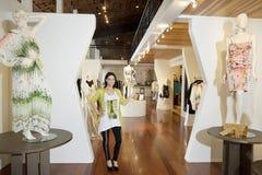 站立与在时尚精品店的时装模特的一名美丽的中间妇女的画象 库存照片