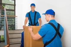 站立与在楼梯的箱子的两名搬家工人 库存图片