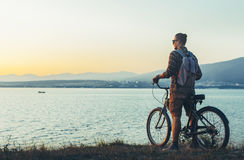站立与在海岸的自行车和享受日落假期旅行的目的地休息的概念的看法年轻人骑自行车者 库存照片
