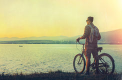 站立与在海岸的自行车和享受日落假期旅行的目的地休息的概念的看法年轻人骑自行车者 免版税库存图片