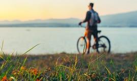 站立与在海岸的自行车和享受自然日落假期旅行的目的地的看法无法认出的人骑自行车者休息C 库存图片