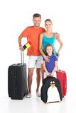 站立与在白色背景的行李的愉快的家庭 免版税库存图片