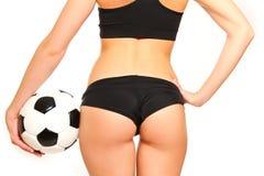 妇女站立与在白色背景的一个足球的,后方vi 免版税库存图片